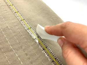 Instructional photo how to score stitch lines with fabric marker for slow embroidered tea towel